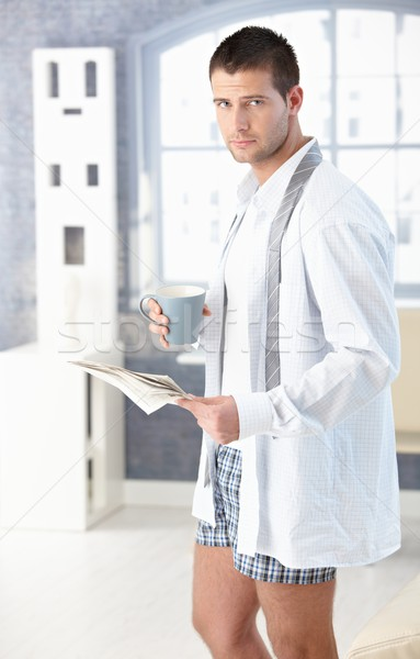 Stock photo: Young man with newspaper and tea in the morning