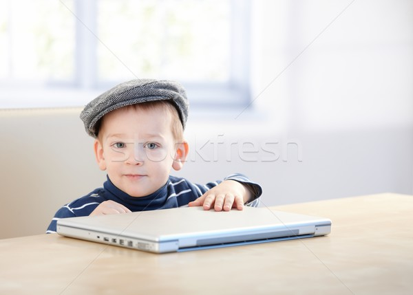 Adorable ginger boy in cap playing with laptop Stock photo © nyul
