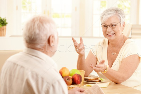 Stock photo: Elderly wife chatting to husband at breakfast