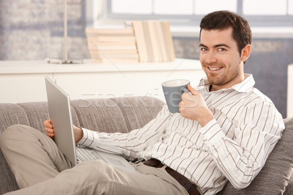 Young man browsing Internet at home smiling Stock photo © nyul