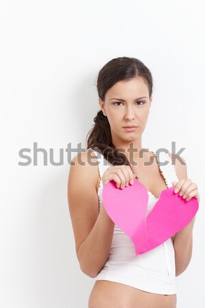 Lovelorn female pulling a paper heart to pieces Stock photo © nyul