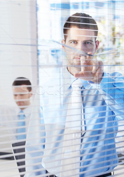 Handsome businessman peeping through blind Stock photo © nyul