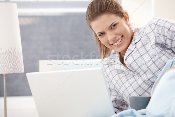 Happy woman in pyjama using laptop Stock photo © nyul