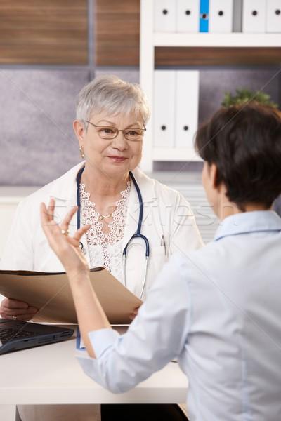 Beteg ül orvosi rendelő gesztikulál mosolyog orvos Stock fotó © nyul