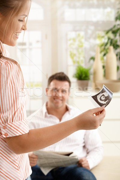 Smiling woman showing ultrasound picture to man Stock photo © nyul