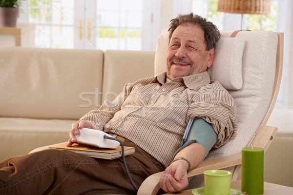Stock photo: Elderly man measuring blood pressure
