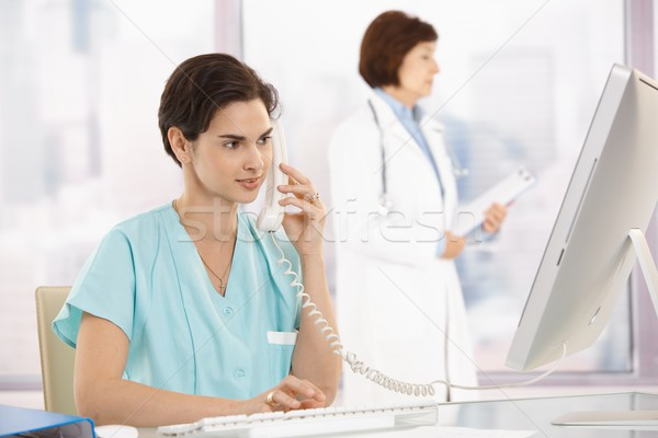Stock photo: Medical assistant on phone, using computer
