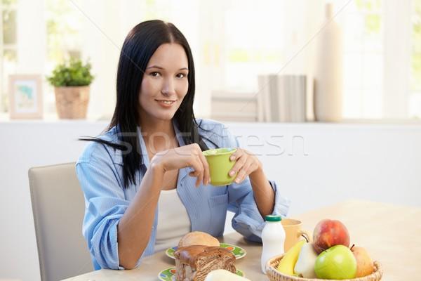 Stock fotó: Gyönyörű · nő · reggeli · asztal · mosolyog · ül · tart