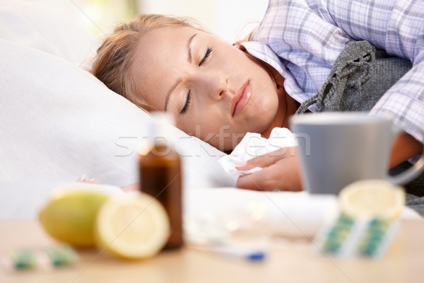 Stock photo: Young female caught cold laying in bed sleeping