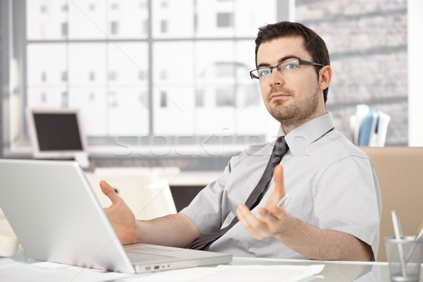 Young stock broker using laptop gesturing Stock photo © nyul