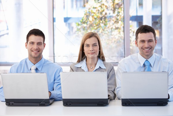 Stock photo: Happy businessteam working on individual laptops