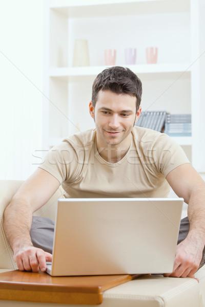 Boldog férfi számítógép fiatal póló ül Stock fotó © nyul