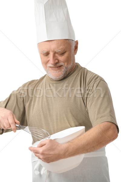 Senior chef whisking egg in kitchen Stock photo © nyul
