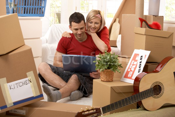 Happy couple looking at computer in new house Stock photo © nyul