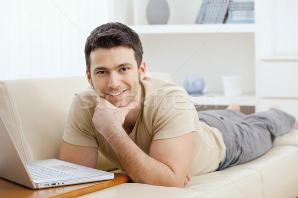 Man met behulp van laptop home gelukkig jonge man leggen Stockfoto © nyul