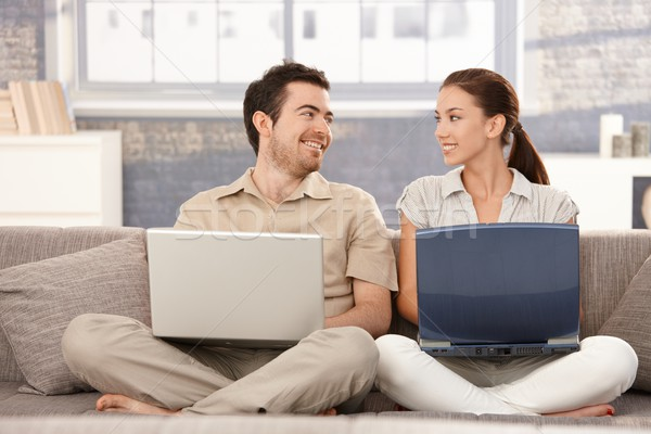 Happy couple browsing internet having fun smiling Stock photo © nyul
