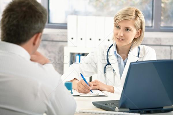 Médecin prendre des notes patient parler bureau souriant Photo stock © nyul