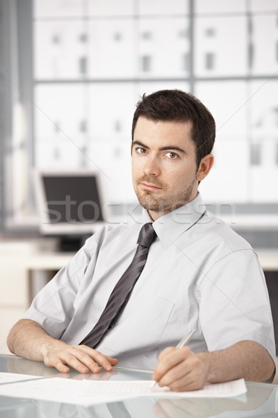 Stock photo: Young businessman sitting at desk writing notes