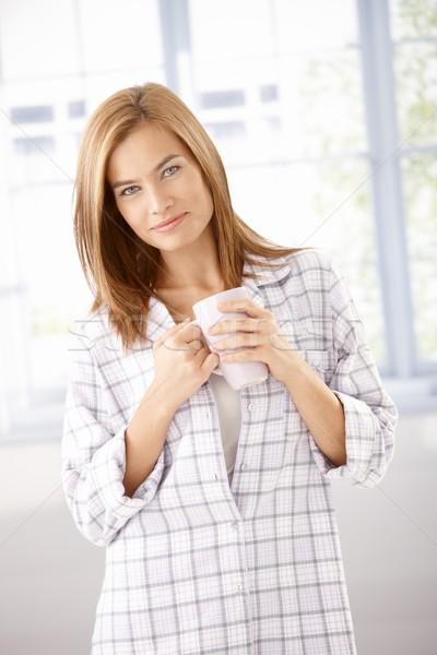 Attractive girl in pyjama drinking tea smiling Stock photo © nyul