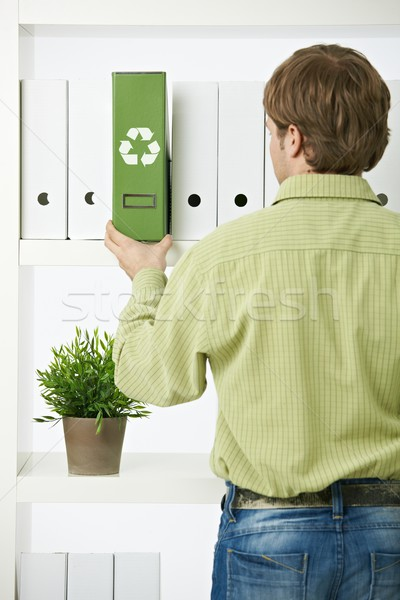 Young man pulling out green folder Stock photo © nyul