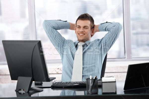 Satisfied businessman smiling at desk Stock photo © nyul