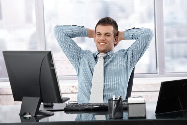 Satisfeito empresário sorridente sessão secretária brilhante Foto stock © nyul