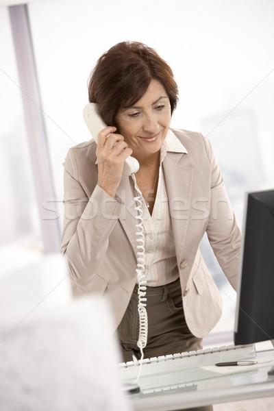 Zdjęcia stock: Starszy · kobieta · interesu · biurko · uśmiechnięty · mówić · telefonu