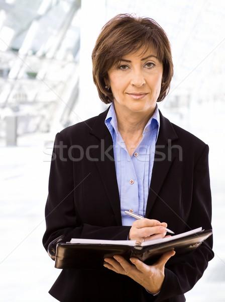 Starszy kobieta interesu piśmie zauważa uśmiechnięty patrząc Zdjęcia stock © nyul