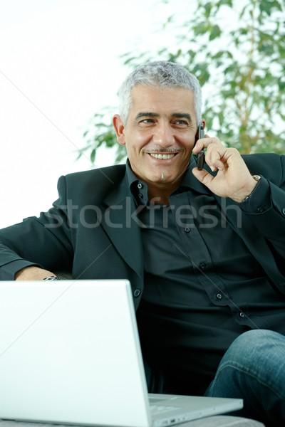 Empresário falante telefone móvel cinza maduro sessão Foto stock © nyul