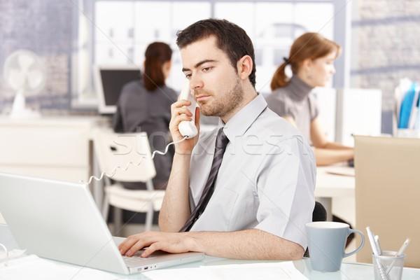 Młodych pracownik biurowy za pomocą laptopa mówić telefonu posiedzenia Zdjęcia stock © nyul