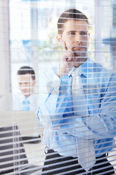 Young businessman looking through blind thinking Stock photo © nyul