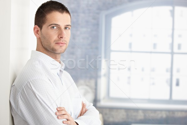 Stock photo: Handsome young man standing arms crossed