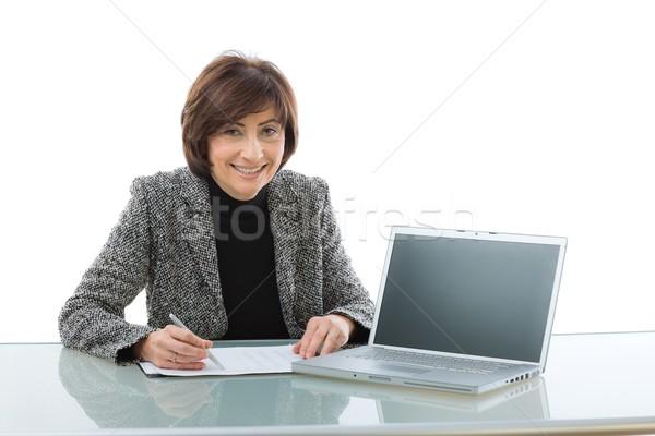Senior imprenditrice presentazione seduta desk utilizzando il computer portatile Foto d'archivio © nyul