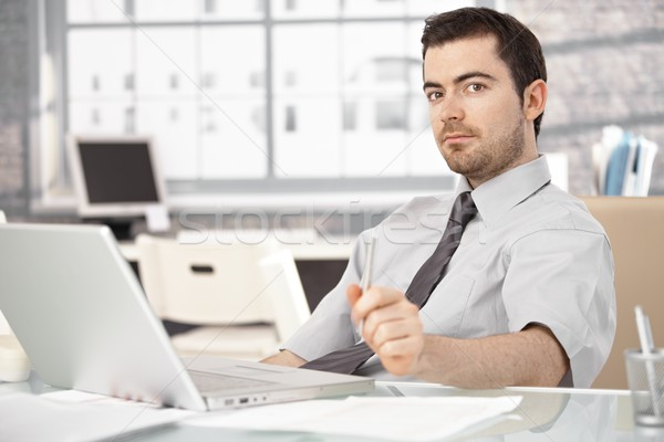 Young man sitting at desk using laptop Stock photo © nyul