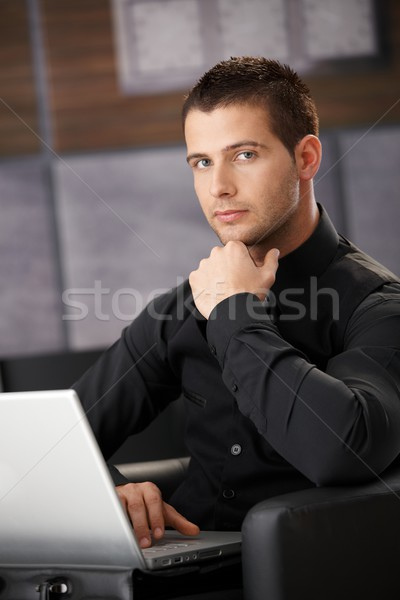 Businessman in black working on laptop Stock photo © nyul
