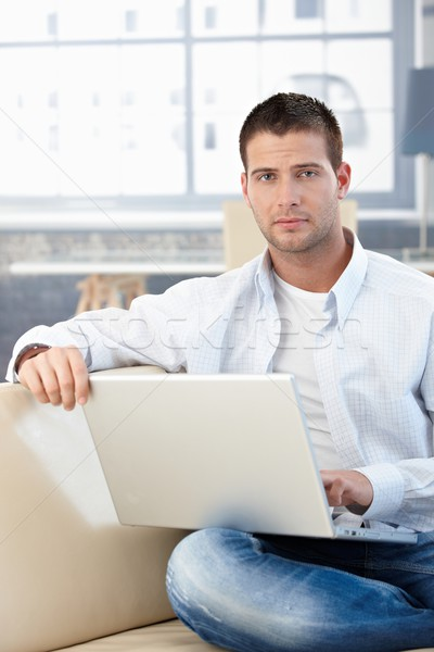 Goodlooking man working at home on laptop Stock photo © nyul