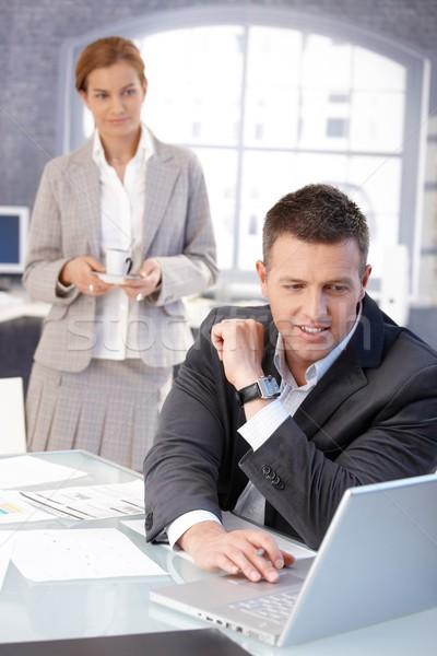 Businessman working at desk getting coffee Stock photo © nyul