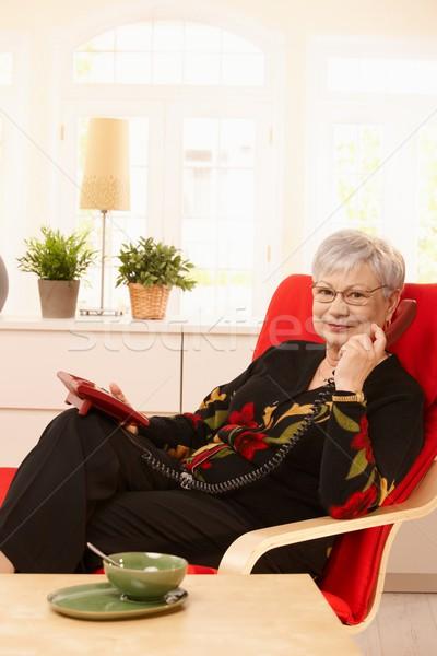 Rentner Dame Telefon Sitzung Sessel lächelnd Stock foto © nyul