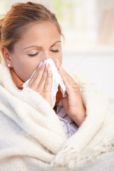 Stock photo: Young woman having flu blowing her nose