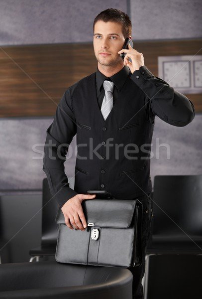 Handsome businessman in office lobby with mobile Stock photo © nyul