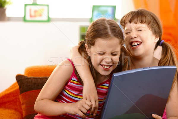 Cute girl friends laughing at laptop Stock photo © nyul