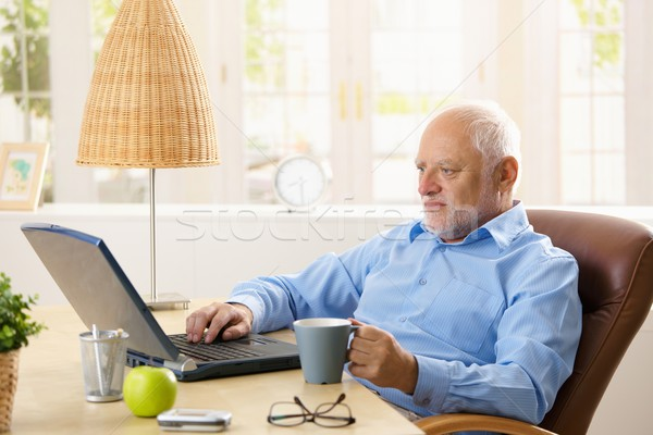 Elderly man using computer, having coffee Stock photo © nyul
