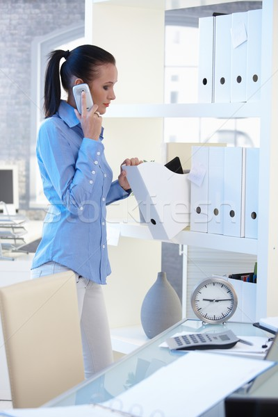 Office girl on phone call checking folders Stock photo © nyul