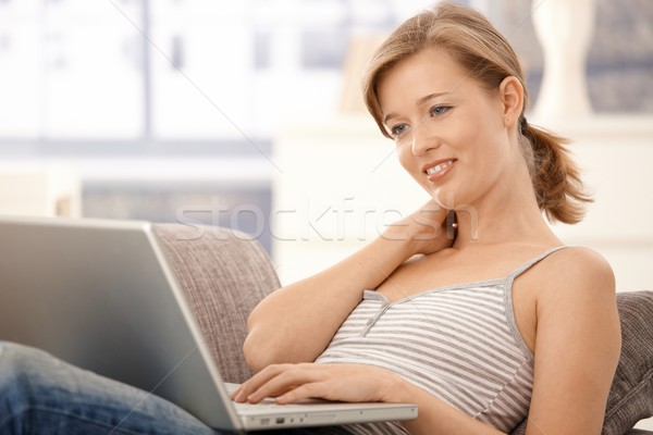 Stock photo: Happy young woman browsing internet at home