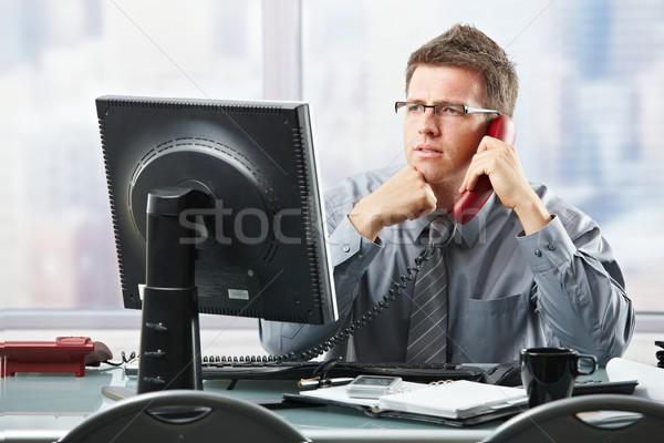 Businessman listening to landline call in office Stock photo © nyul