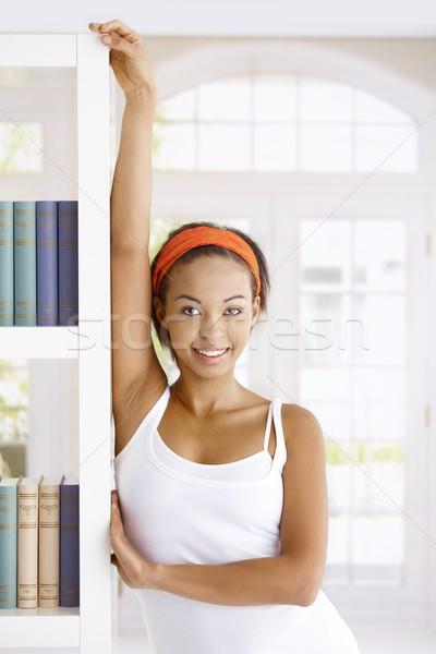 Aantrekkelijke vrouw boek poseren boekenplank home glimlachend Stockfoto © nyul