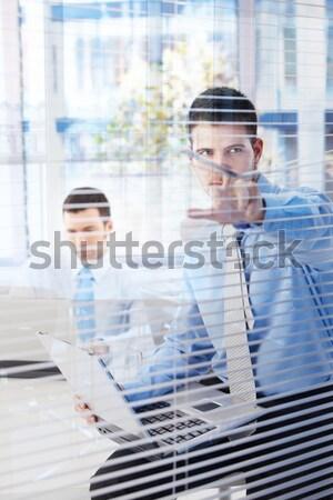 Nosy businesswoman looking through blind Stock photo © nyul
