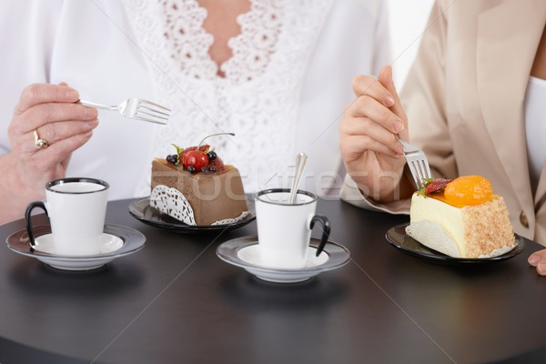 Café duas mulheres sessão mesa de café alimentação bolo Foto stock © nyul