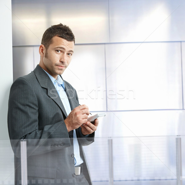 ストックフォト: ビジネスマン · スマートフォン · 深刻 · 立って · 現代 · オフィス