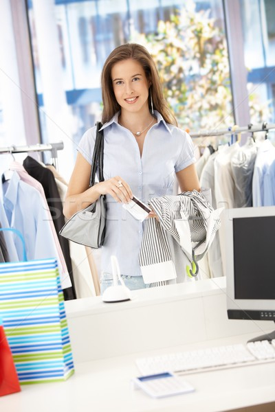 Happy woman paying in clothes store Stock photo © nyul